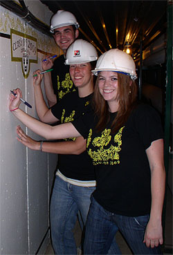 Graduating seniors signing a wall in the tunnels beneath Gustavus.